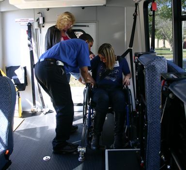 Wheelchair securement training. Operator secures passenger.